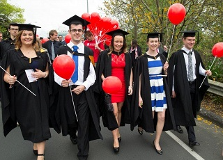 Five students parading in street procession at graduation