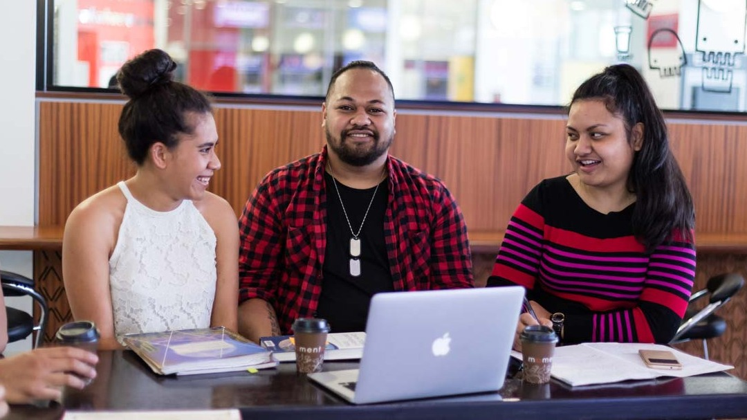 Three Pacific students sitting around a table in front of a laptop