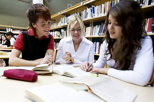 three young women studying together at a table in the library