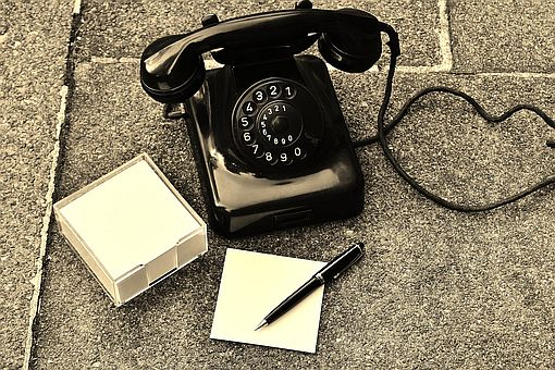 old fashioned phone sitting on pavement with paper pad and pen. Link to contact us information