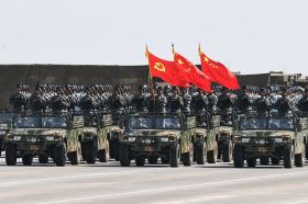 Chinese soldiers in vehicles wave flags