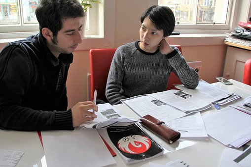 Two students consulting together at a desk over an assignment