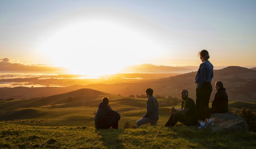 Group of students sitting on a mountain watching the sunrise