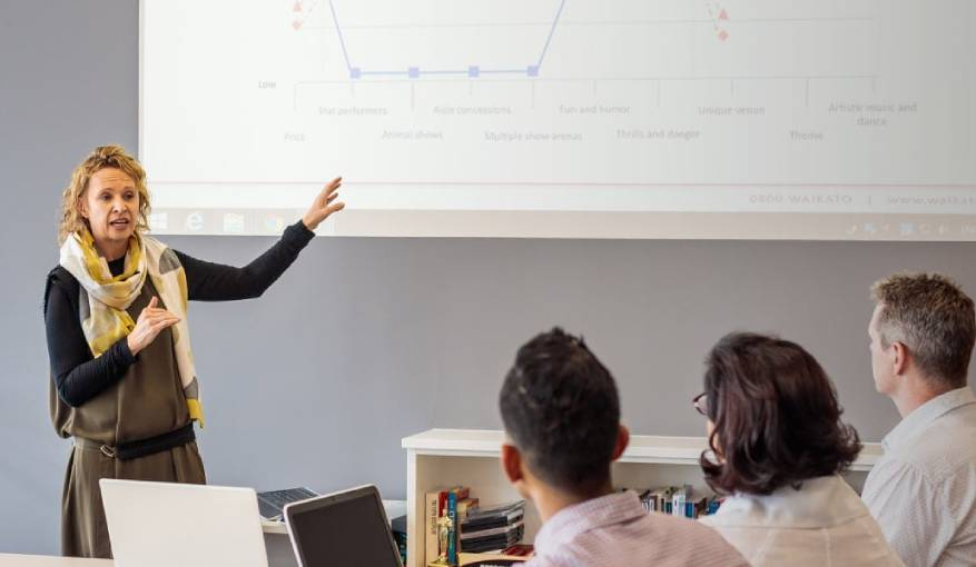 lady speaking in a classroom and pointing to a powerpoint
