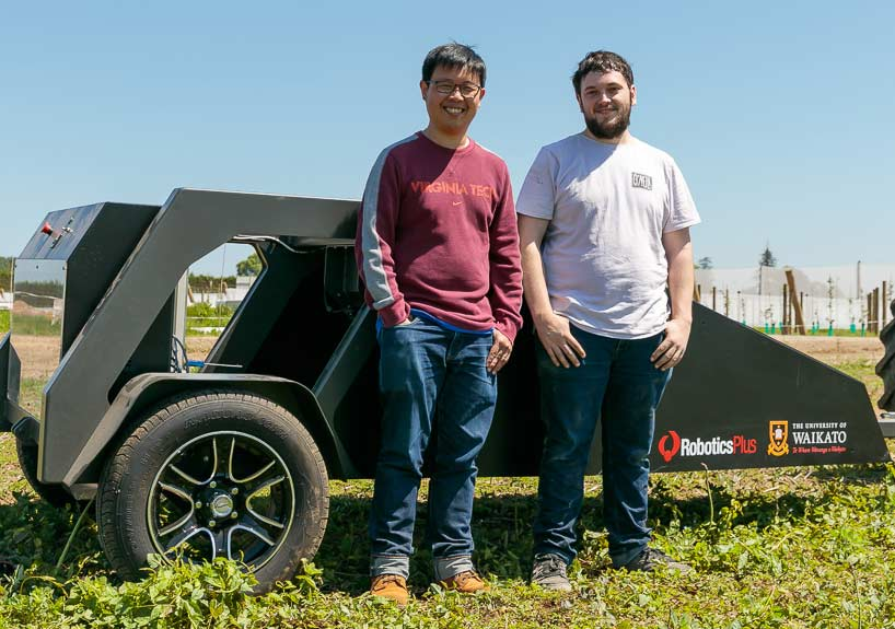 Two students standing next to asparagus picker machine.