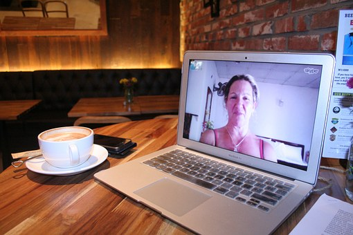 laptop and coffee on a desk, woman skyping on laptop