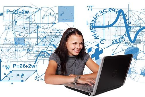 woman with laptop on white background with whiteboard behind her covered in mathematical symbols