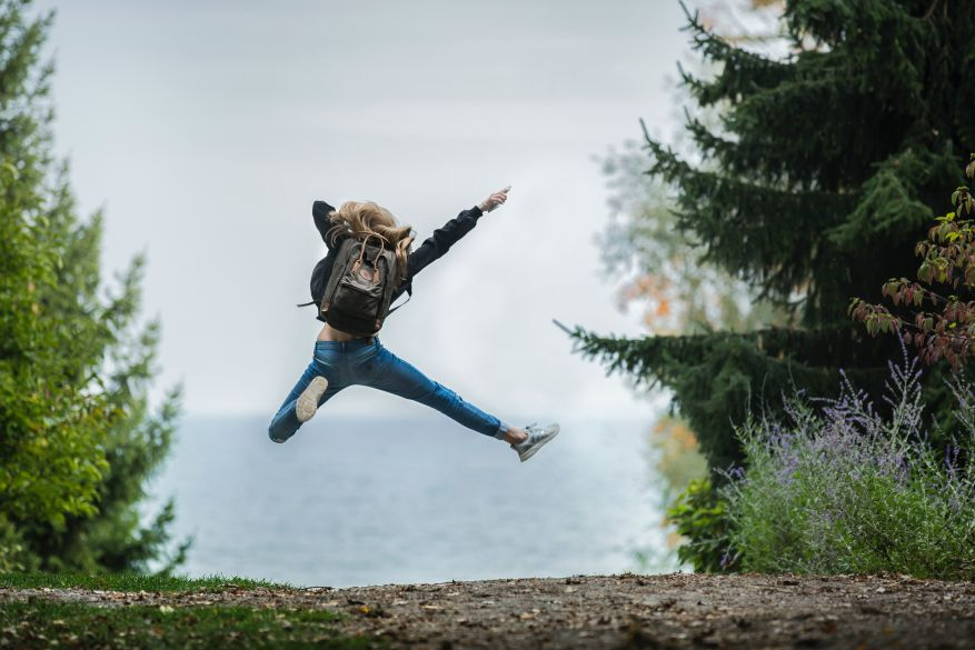 Girl jumping on a forest path