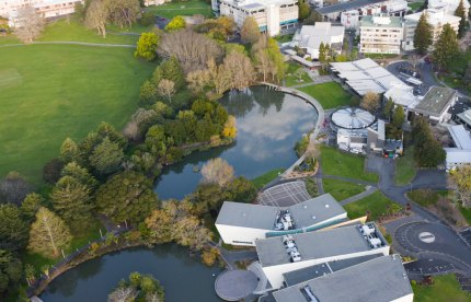 Drone photo of the Waikato campus showing trees, field and lakes