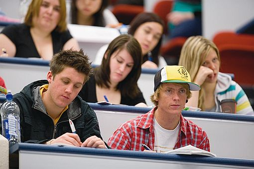 University students sitting an exam in a lecture theatre
